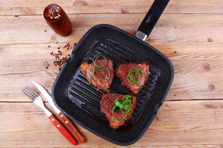 fresh grilled bloody beef steaks on black grill plate on wood photo