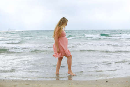 A young pregnant blond woman posing on a light blue sea background photo
