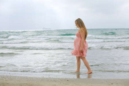 Portrait of a young beautiful blond pregnant woman at beach . on sea background. photo