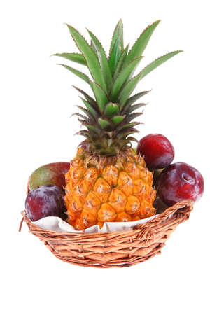 diet food - a lot of fresh raw tropical fruits include pineapple plum and mango in small basket isolated over white background photo