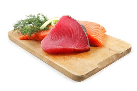 piezas de salmón y atún en un plato de madera aislada sobre fondo blanco