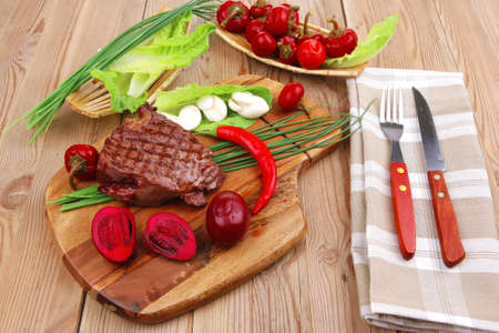barbecued meat : beef ( lamb ) garnished with green lettuce and red chili hot pepper on wooden table with cutlery photo