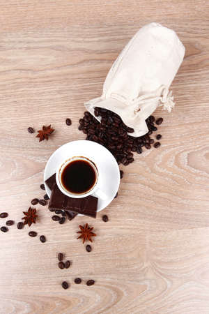 sweet hot food: black coffee with dark chocolate and coffee beans in bag on wooden table Stock Photo - 16990218