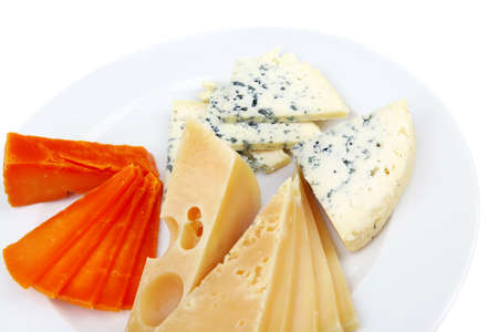 cheeseboard: fresh aged french cheese parmesan roquefort and gruyere chops with slices on plate with isolated over white background
