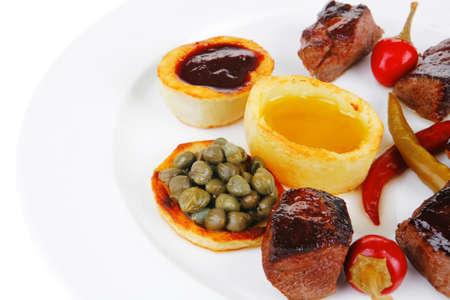 european food: europeo de alimentos: carne de res a la parrilla en plato de porcelana blanco aislado en fondo blanco pimiento picante, alcaparras y salsas