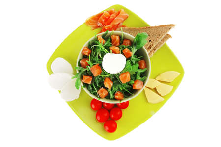 green salad with salmon and tomatoes on plate photo