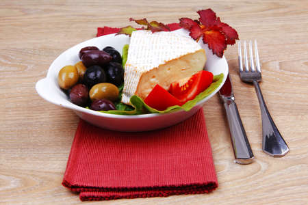 aged brie cheese on salad in white dish over red cloth on with olives and tomato over wooden table photo