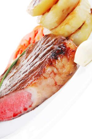 meat savory : grilled beef fillet steak on white plate with tomatoes , potatoes and chives isolated over white background photo