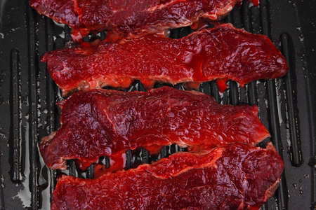 raw bloody beef fillet steaks on black grill plate isolated on white background photo