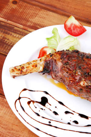 meat on wooden plate : roast shoulder on wood with tomatoes chives and green lettuce on white plate photo