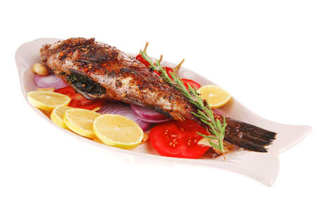 served main course: whole fried seabass served on plate with lemons,tomatoes and peppers Stock Photo - 17071592