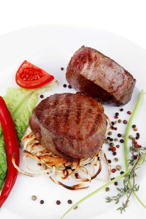 bbq background: grilled beef fillet with thyme , red hot chili pepper and tomato on plate isolated over white background Stock Photo