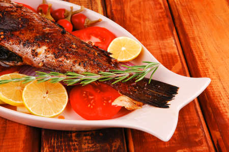 whole fried bass on plate, served with lemons and tomatoes Stock Photo - 17460456