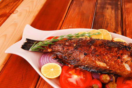 savory: whole fryed sunfish over wood with tomatoes lemons and peppers Stock Photo - 17460439