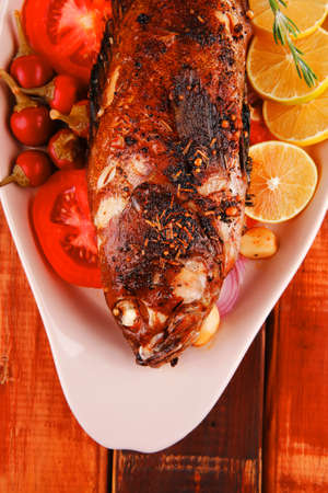 main course: whole fried seabass served on wood with lemons,tomatoes and peppers Stock Photo - 17460485