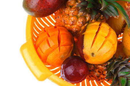 diet food - a lot of fresh raw tropical fruits include pineapple red plum and green mango in orange colander isolated over white background photo