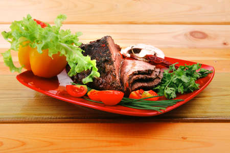 beef on red plate with vegetables over wood photo