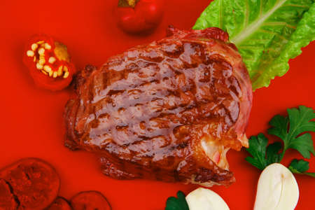 meat food : roast beef garnished with green lettuce and red chili hot pepper on red plate isolated over white background photo
