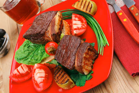 roast meat : beef (pork) steak garnished with vegetables , juice and olives on red plate over wooden table photo