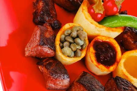 european food: alimentaria europea: roast beef carne goulash sobre placa roja aislada en el fondo blanco con tomate y eneldo y salsa de barbacoa Foto de archivo