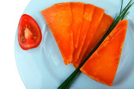 tabla de quesos: anaranjado cheddar envejecido deliciosa tajada de queso con rebanada en un plato azul con los tomates y las cebolletas aisladas sobre fondo blanco