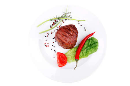 grilled beef fillet medallions on noodles with red hot chili pepper and salad leaf on white plate isolated over white background Stock Photo - 17524831