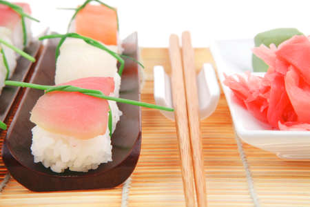 Japanese Cuisine - Different Types of Nigiri Sushi : Tuna (maguro) Salmon (sake) and Eel (unagi) with Wasabi and Ginger on bamboo mat isolated over white background photo
