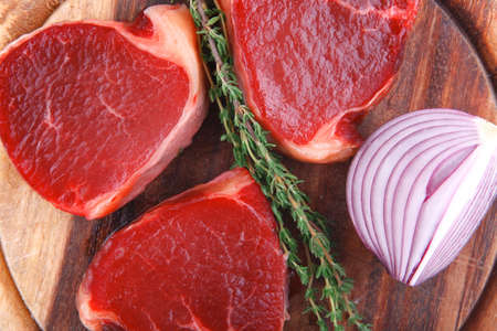 steak beef: fresh raw beef fillet medallions with thyme twig on wooden plate isolated over white background Stock Photo