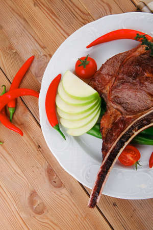 meat food : grilled beef spare rib on white dish with thyme pepper and tomato on wooden table Stock Photo - 17527763
