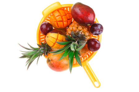 diet food - a lot of fresh raw tropical fruits include pineapple red plum and green mango in orange colander isolated over white background Stock Photo - 17527611