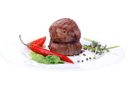 grilled beef fillet medallions on noodles with red hot chili pepper and salad leaf on white plate isolated over white background Stock Photo - 17528138