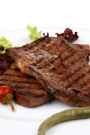 meat food : two roast steak boneless with red and chili peppers, served on green lettuce salad on dish isolated over white background photo