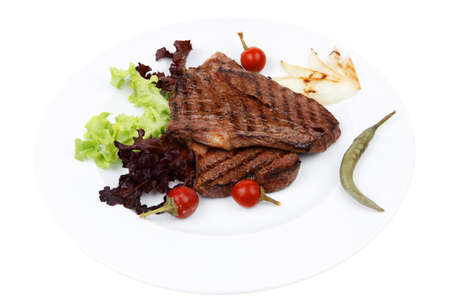 frame less: meat food : two roast steak boneless with red and chili peppers, served on green lettuce salad on dish isolated over white background Stock Photo