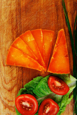 orange aged delicious cheddar cheese chop with slice on wooden plate with tomatoes , chives and salad . isolated over white background photo