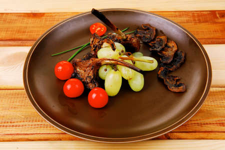roasted ribs on dish over wooden table photo