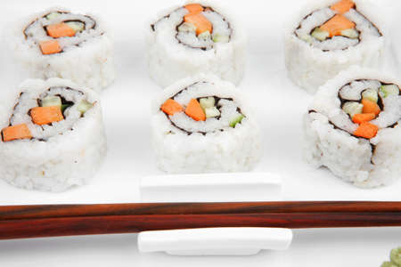Maki Sushi - California Maki Roll made of fresh raw Salmon, Cream Cheese and Avocado inside. Served with wasabi . Isolated over white background on square plate photo