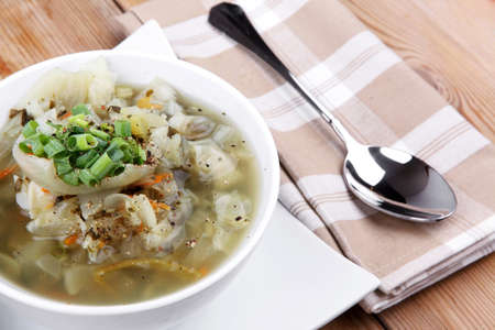 diet food : hot vegetable soup with bread  crackers in white bowl on  stand over wood table photo