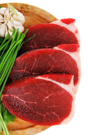 raw meat : fresh beef pork fillet pieces with garlic and green stuff on wood isolated over white background photo