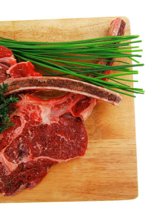 boned: raw meat : boned fresh ribs served with thyme and green chives on wooden board isolated over white background