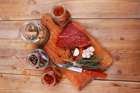 raw beef meat fillet with peppercorn and thyme and differnt spices in glass bottles ready to grill on wood figured aged board over table photo