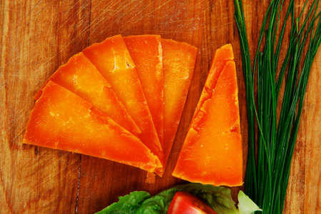 mellow: orange aged delicious cheddar cheese chop with slice on wooden plate with tomatoes , chives and salad . isolated over white background