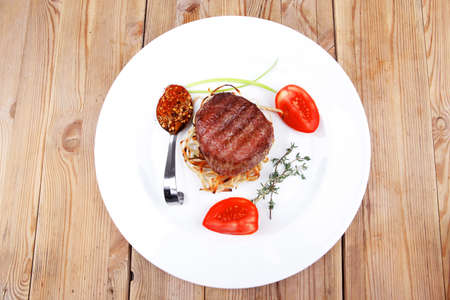 grilled beef fillet pieces on noodles with tomatoes dry spices and green thyme twigs on white plate over wood Stock Photo - 17867466