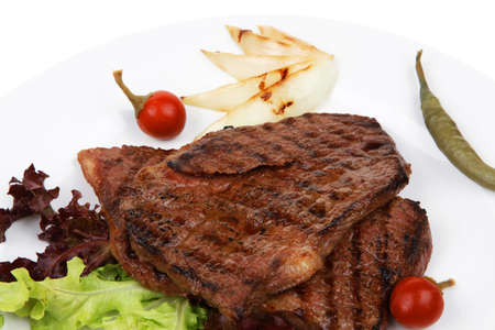 meat food : two grilled steak with chili and red peppers , green lettuce salad , on dish isolated over white background photo