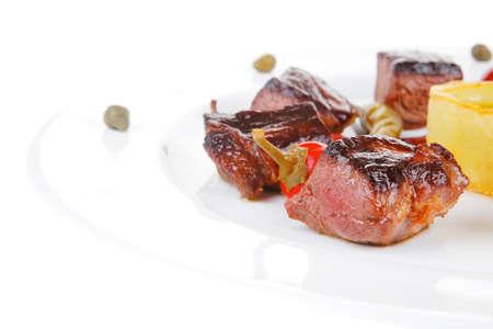 european food: alimentaria europea: roast beef carne goulash sobre la placa redonda blanca aislada sobre fondo blanco con pimienta roja picante, alcaparras y salsas