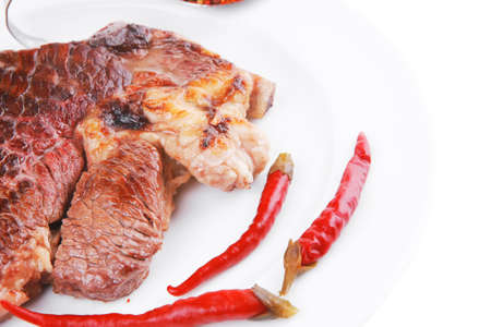 meat food : grilled beef steak on white plate with red thin pepper , spices and rosemary isolated over white background photo