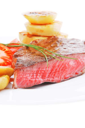 meat food : roasted fillet on white plate with tomatoes and chives isolated over white background photo