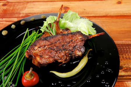sawory on black: grilled ribs on plate over wooden table Stock Photo - 18187562