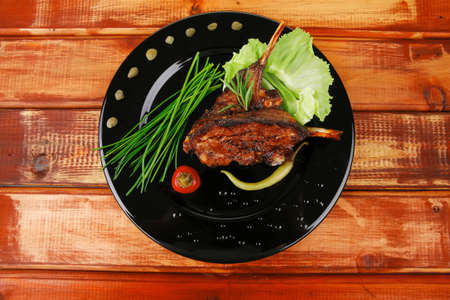 sawory on black: grilled ribs on plate over wooden table Stock Photo - 18187744