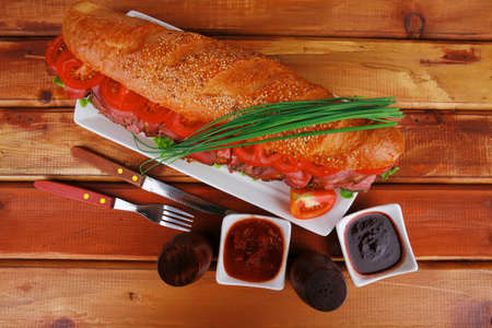 sandwich on plate : french baguette with smoked sausage on white plate over wooden table photo