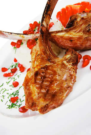 meat savory: roast veal ribs with rice garnish and pomegranate seeds over white background photo